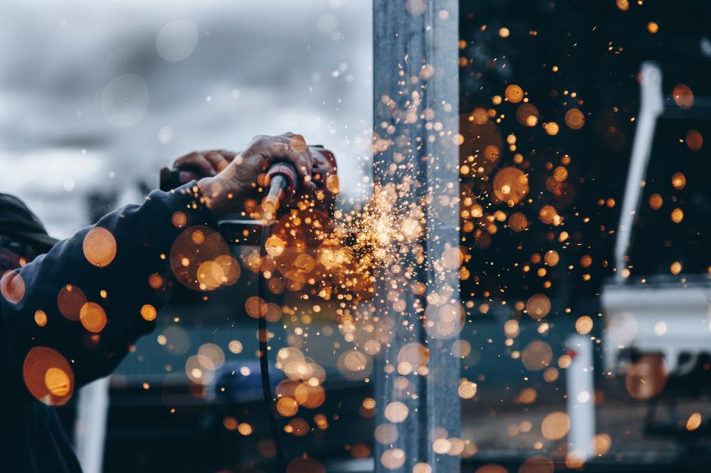 photo of a steel worker sparks with metal grinder